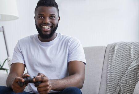 Foto de Millennial african american guy playing video games at home, holding joystick in hands, free space - Imagen libre de derechos
