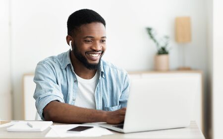 Photo pour Smiling african-american guy in earphones studying foreign language online through video conference application, panorama with copy space - image libre de droit