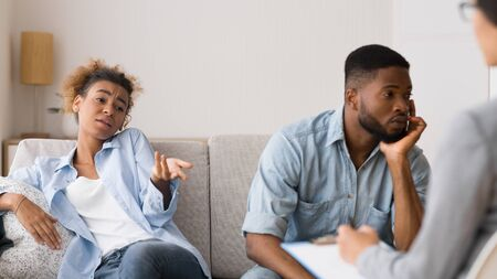 Foto de Sexual Problems And Impotence. Indifferent African American Wife Complaining To Sexologist About Stale Sex Sitting On Couch With Husband, Panorama - Imagen libre de derechos