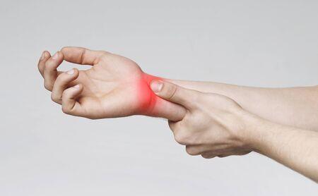 Foto de Millennials disease. Young man suffering from carpal tunnel syndrome, touching painful wrist, panorama - Imagen libre de derechos