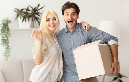 Foto de New House Owners. Loving Couple Hugging Holding Key And Moving Box. Free Space - Imagen libre de derechos