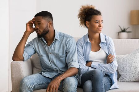 Foto de Misunderstanding In Relationship. Frustrated Black Man And Woman Avoiding Eye Contact Sitting On Couch At Home. - Imagen libre de derechos
