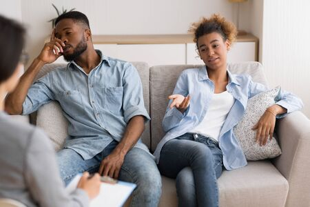 Foto de Indifference In Marriage. African American Wife Blaming Her Husband Sitting With Him On Sofa At Marital Therapists Office. - Imagen libre de derechos