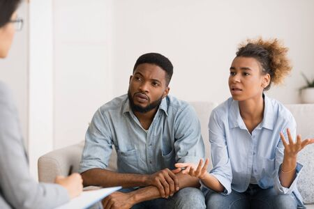 Photo pour African American Wife Talking To Counselor Sitting On Sofa Next To Husband. - image libre de droit