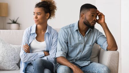 Foto de Not on speaking terms. Frustrated afro couple looking away avoiding eye contact sitting on couch. - Imagen libre de derechos