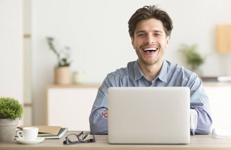 Photo for Man Sitting At Laptop And Laughing Looking At Camera Indoor. Empty Space For Text - Royalty Free Image