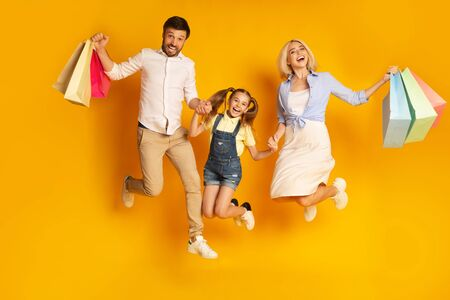 Photo pour Shopping Together. Happy Family Of Three Jumping Holding Shopper Bags Over Yellow Studio Background. - image libre de droit
