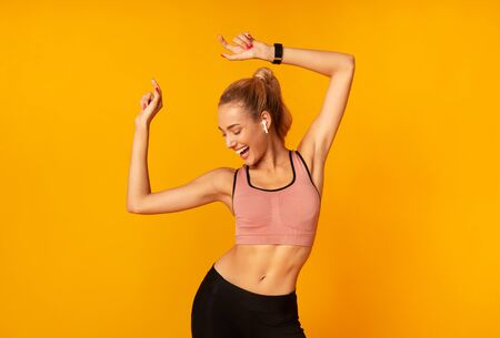 Photo pour Sporty Woman In Wireless Earphones Dancing Listening To Music Over Yellow Studio Background. Free Space - image libre de droit