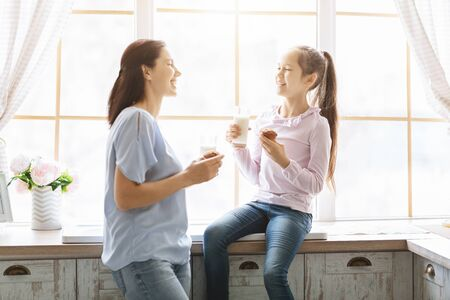 Photo pour Mother and daughter eating muffins and drinking milk near kitchen window, having fun together - image libre de droit