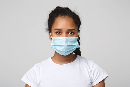Foto de Flu concept. Teen african girl with protective face mask, grey studio background - Imagen libre de derechos