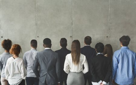 Photo for Businesspeople looking at grey wall with free space, standing in row, back view - Royalty Free Image