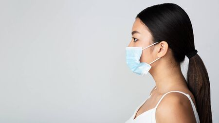 Foto de Asian girl wearing medical mask and looking at free space, grey background, side view - Imagen libre de derechos