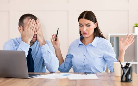 Photo for Professional Incompetence. Businessman Covering Eyes Unable To Train Silly Intern Girl Sitting In Modern Office. - Royalty Free Image