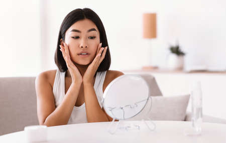 Photo pour Facelift And Skin Care Concept. Portrait Of Young Asian Lady Massaging Her Face Sitting In Front Of The Mirror. Lady Applying Moisturizing Cream, Doing Facial Anti Aging Massage At Home - image libre de droit