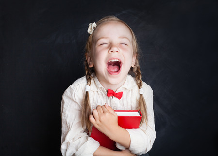 Photo pour Child with book having fun and laughing. Smart child. Love school and education concept - image libre de droit