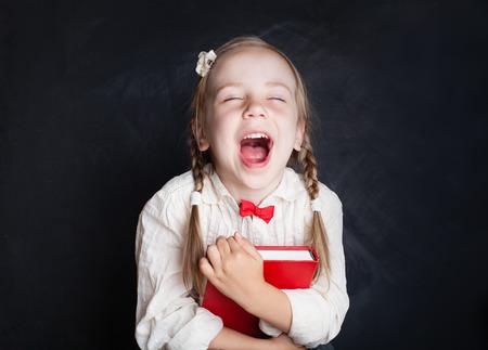 Foto de Child with book having fun and laughing. Smart child. Love school and education concept - Imagen libre de derechos