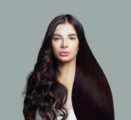 Foto de Beautiful fashion model woman with long straight hair and perfect curly hairstyle on blue background - Imagen libre de derechos