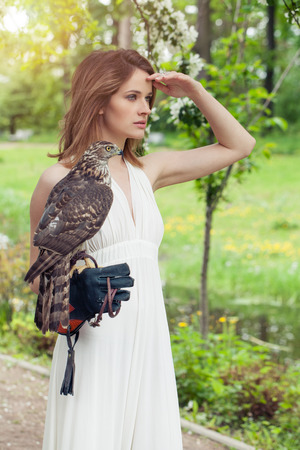 Perfect bride woman in white dress holding bird outdoor