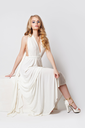 Photo pour Beautiful woman with perfect legs in high heels shoes. Nice model in white dress - image libre de droit
