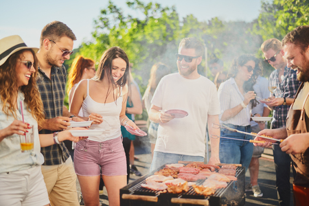 Photo for Group of people standing around grill, chatting, drinking and eating. - Royalty Free Image