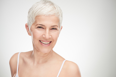 Foto de Portrait of beautiful senior woman in front of white background. - Imagen libre de derechos