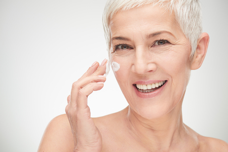 Photo for Head shot of beautiful senior woman putting on the creme. - Royalty Free Image