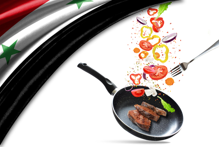 Frying pan with falling vegetables and meat, isolated. On the background of the flag of Syria