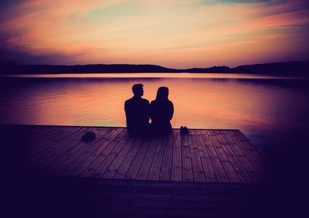 Photo pour Silhouettes of hugging couple against the sunset sky. Vintage photo. - image libre de droit