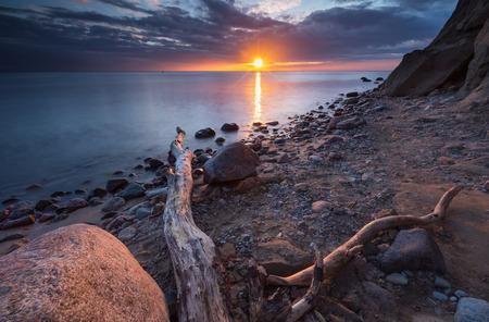 Foto de Beautiful long exposure landscape of rocky sea shore. Tranquil scene of Baltic sea. - Imagen libre de derechos
