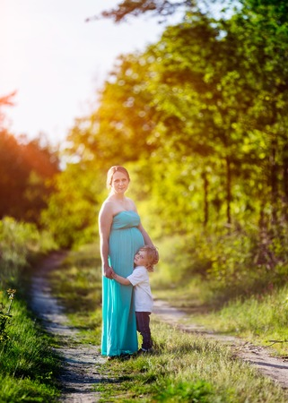 Photo for Pregnant woman outdoor portrait. Beautiful caucasian pregnant woman and shes older son - Royalty Free Image
