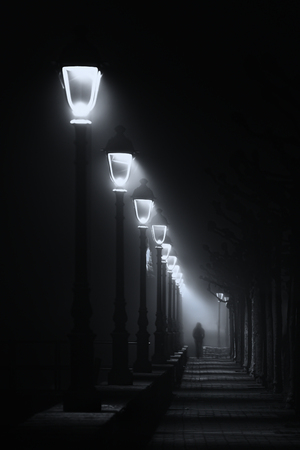 Photo for person walking on dark street illuminated with streetlamps. Black and white - Royalty Free Image