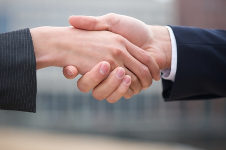Businessman and business woman handshake close up