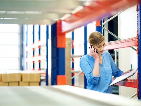Photo for Portrait of a businesswoman on the phone and checking inventory in warehouse - Royalty Free Image