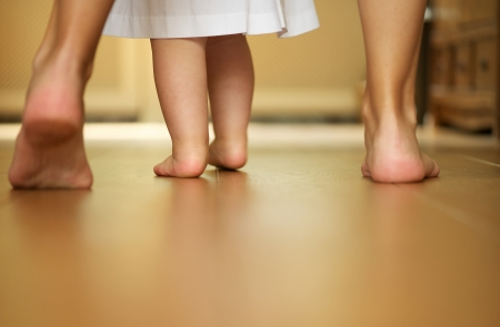 Photo for Closeup portrait of a mother teaching baby to walk indoors - Royalty Free Image