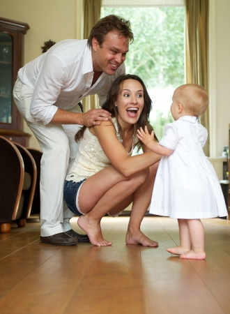 Photo for Portrait of a couple of happy parents helping baby take first steps - Royalty Free Image
