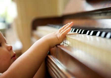 Photo for closeup portrait of a baby playing the piano - Royalty Free Image