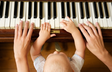 Photo for Closeup portrait of a baby learning to play piano with mother - from above - Royalty Free Image