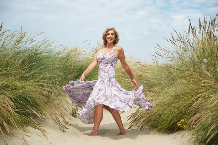 Foto per Portrait of a beautiful middle aged woman dancing in the sand at the beach - Immagine Royalty Free
