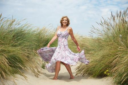 Foto für Portrait of a beautiful middle aged woman dancing in the sand at the beach - Lizenzfreies Bild