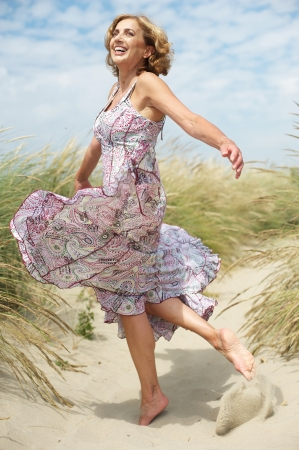 Foto de Carefree portrait of a beautiful middle aged woman dancing outdoors - Imagen libre de derechos