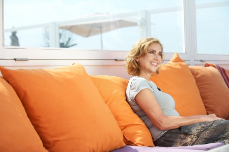 Foto per Closeup portrait of an attractive middle aged woman sitting on sofa outdoors - Immagine Royalty Free