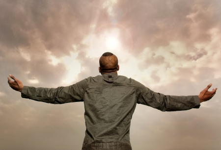 Photo pour Portrait of a man with outstretched arms looking at the sky - image libre de droit