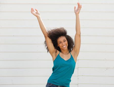 Foto de Portrait of a joyful young woman with arms up in the air - Imagen libre de derechos