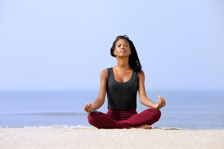 Photo pour Portrait of a beautiful young woman sitting in yoga pose at the beach  - image libre de droit
