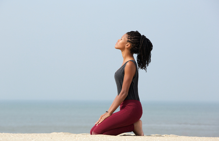 Photo pour Portrait of a beautiful young african american woman meditating at the beach enjoying summer - image libre de droit