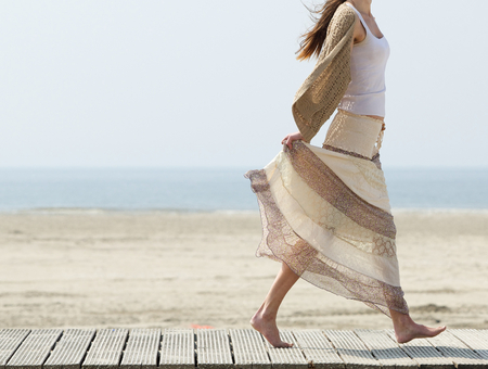 Photo for One female walking at the beach barefoot with dress - Royalty Free Image