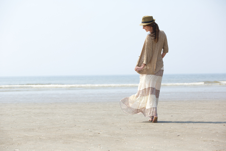 Photo for Rear view portrait of a beautiful woman walking on the beach - Royalty Free Image