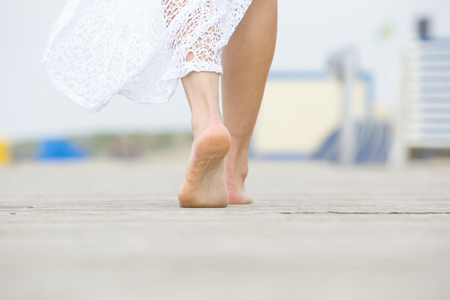 Photo for Close up low angle barefoot woman walking away - Royalty Free Image