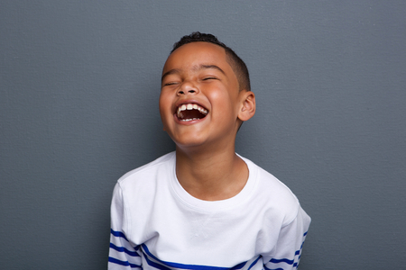 Photo pour Close up portrait of an excited little boy laughing on gray background - image libre de droit