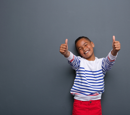 Portrait of a little boy laughing with thumbs up sign on gray background